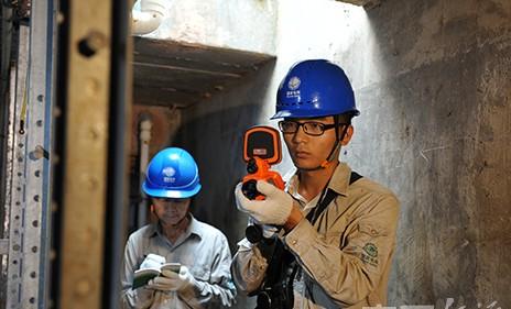 巡视人员手持红外测温仪,对地下电缆进行红外测温。
